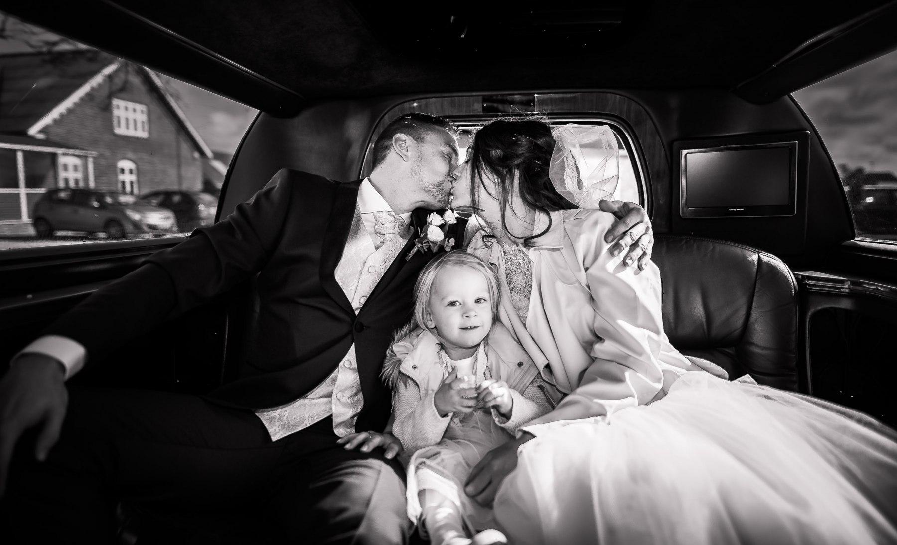 Brudepar kysser i limousine