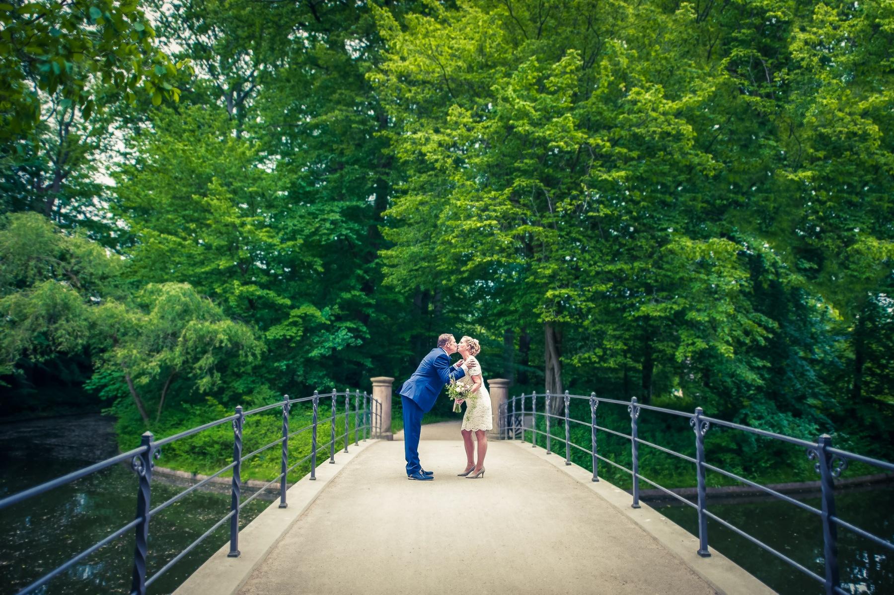 Brudepar kysser på bro i park. København