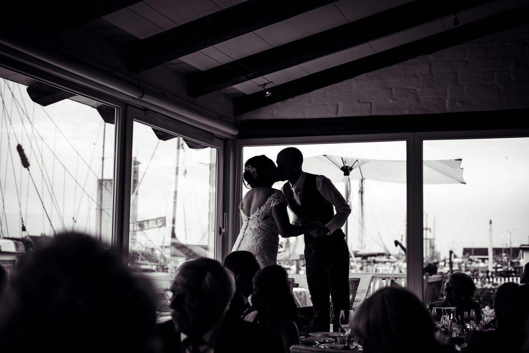brudepar kysser i festsal. Bryllupsfoto