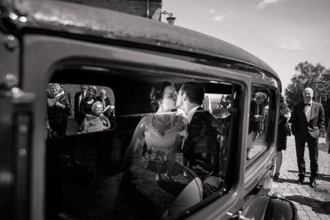 Bryllupsfoto. Brudepar kysser i bil. Billede skudt igennem halvåben bilrude