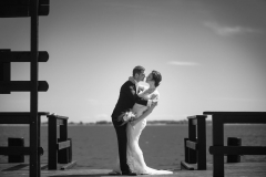 Brudepar kysser på stranden. Bryllupsfoto