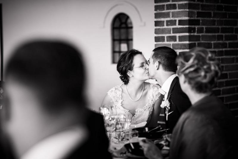 Brudepar kysser i skjul. Bryllupsfoto. Fyn