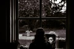 Brud gør sig klar i vindue og spejl. Bryllupsbillede