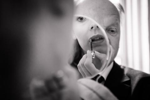 Brud gør sig klar. Far holder spejl. Bryllups fotograf